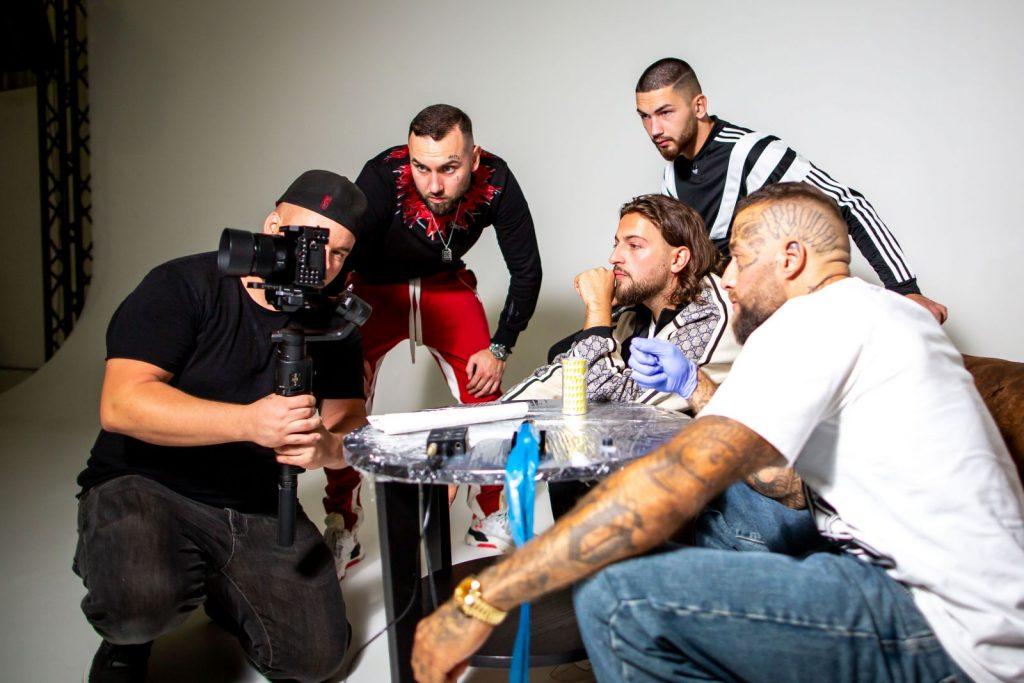 alt=Die Jungs vom Lux Movie Musikvideodreh beim tattowieren