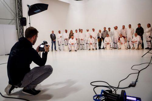 alt=Die Crew des Malerbetriebs gruppiert sich vor dem Fotografen und lächeln in die Kamera